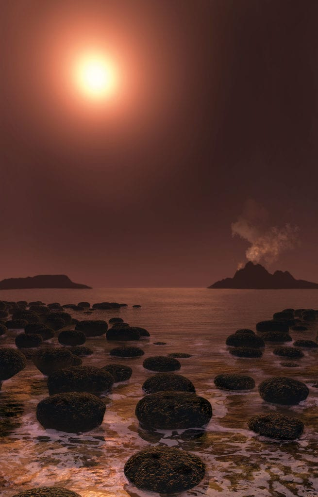 A dim sun shines through haze, with volcanoes in the background and the ocean lapping against mats of organisms called stromalites, in this view of what Earth likely looked like billions of years ago. In the early days of Earth the sun was too dim to keep the planet warm. And yet, evidence shows vast, unfrozen oeans existed when temperatures should have been below freezing.